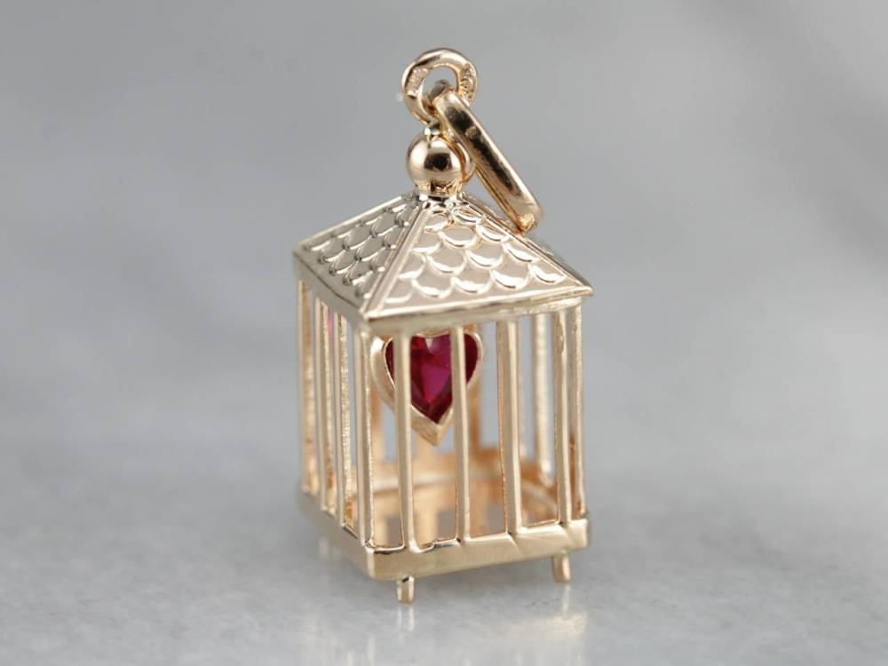 Heart in a Cage - Sentimental charms, such as this heart in a cage or a heart shaped locket, symbolize loyalty to a romantic partner, or otherwise protection of one's love.